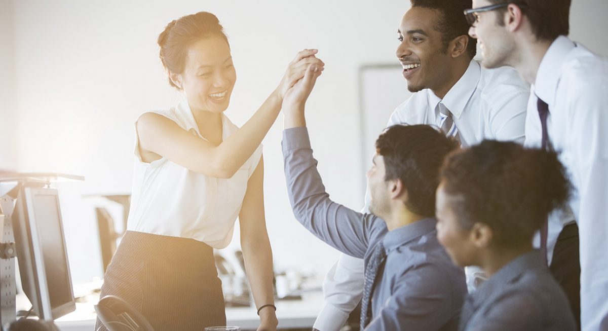 woman high fives colleagues