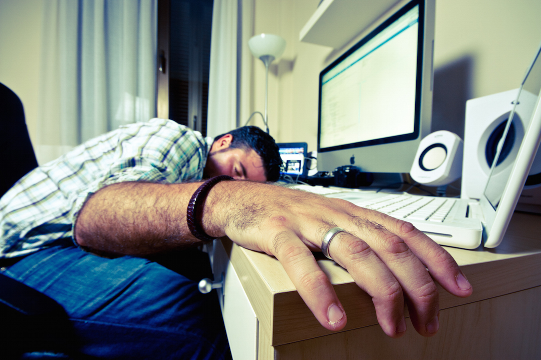 man passed out on computer desk