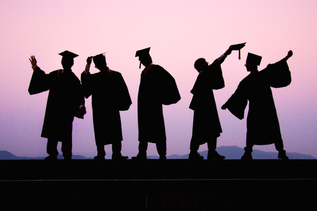 graduate silhouettes in front of pink sky