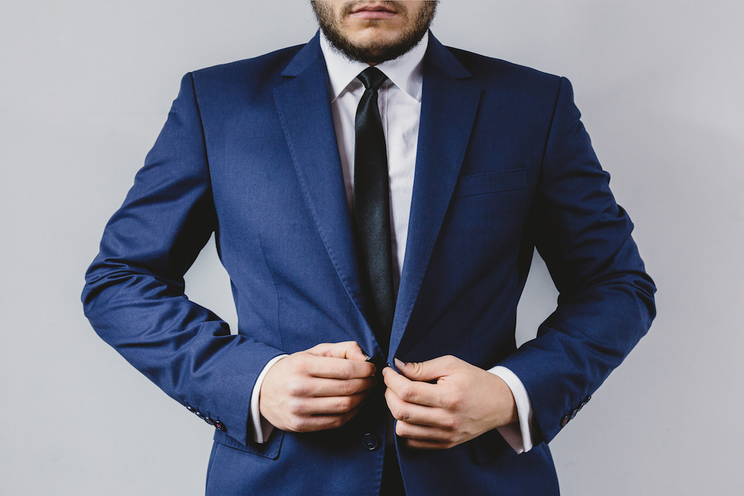 Man in blue jacket buttoning suit