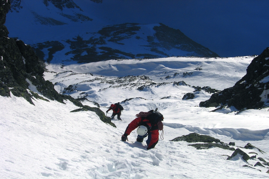 2 climbers climbing up snowy mountain.