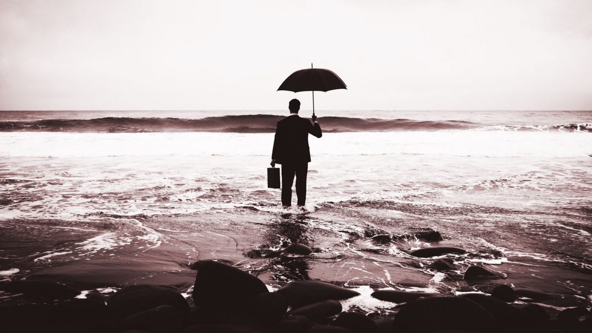 Person standing in ocean with umbrella