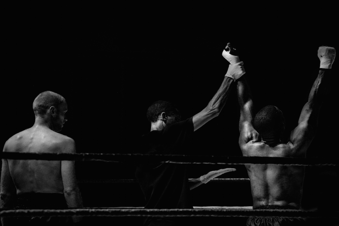 black and white boxing match image with one guy holding up the other's hand.