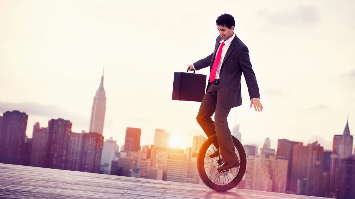 Guy riding unicycle in front of city at sunset