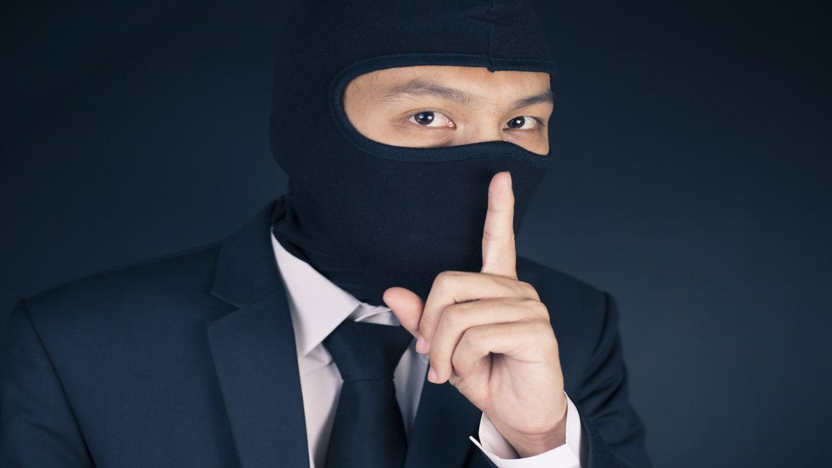 Person in mask holding finger over mouth