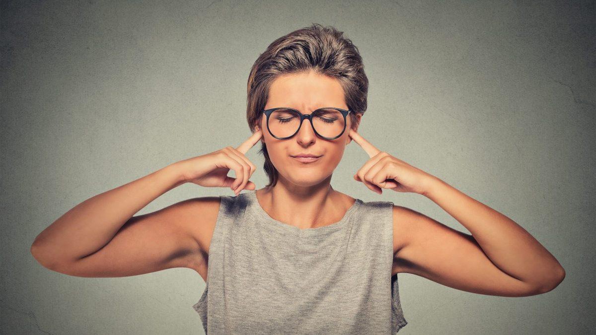 woman blocking ears and closing eyes