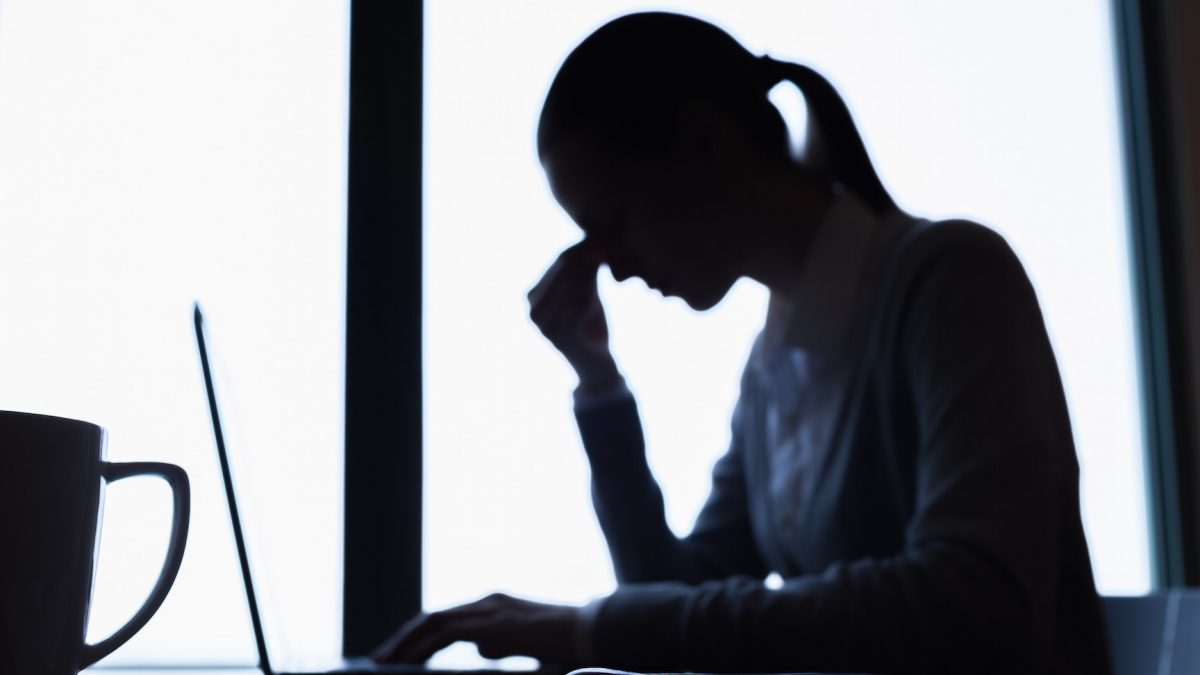 Silhouette of woman with computer and coffee