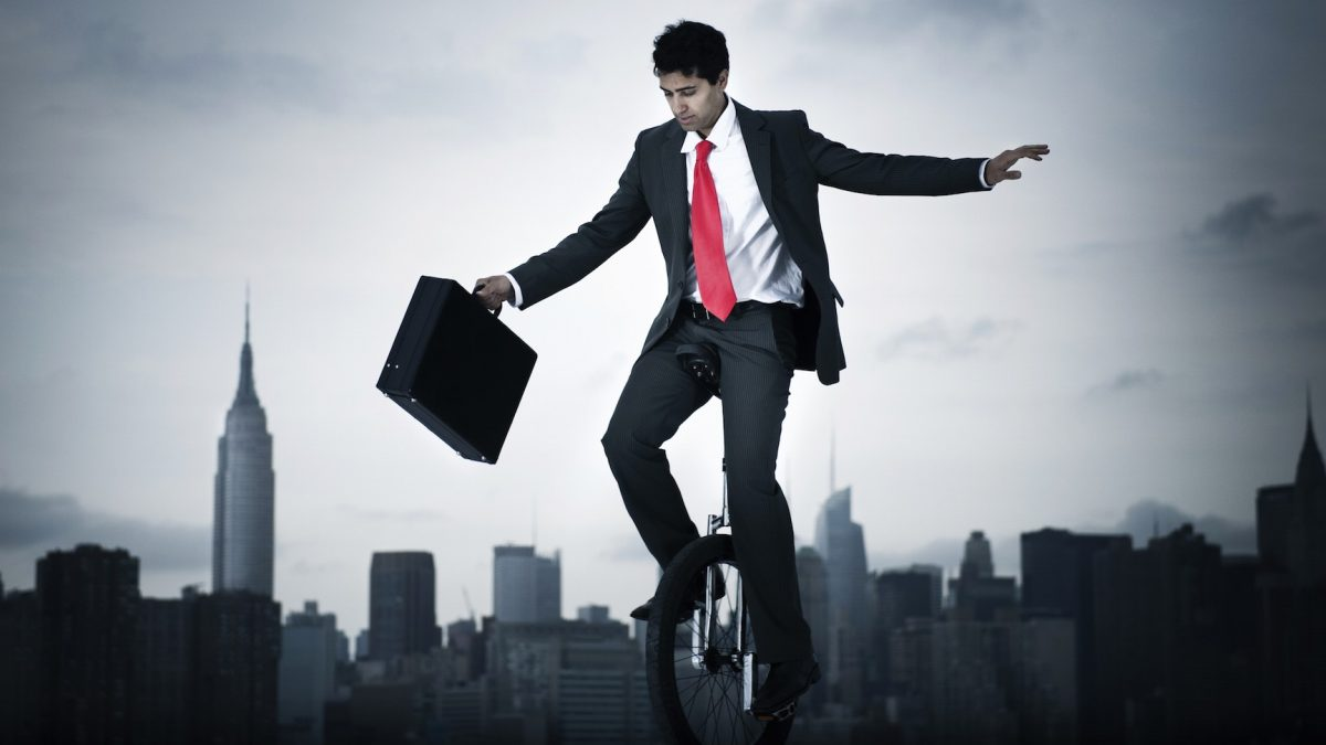 man in red tie on unicycle