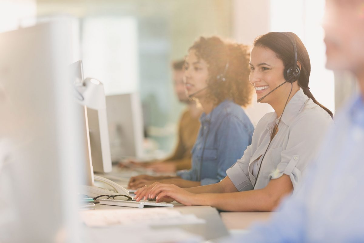 Customer service agents at computer and on phone
